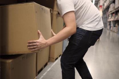 Homme se baissant pour porter un carton
